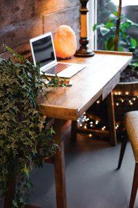 himalayan-salt-lamp-near-laptop-on-wooden-table-3653849